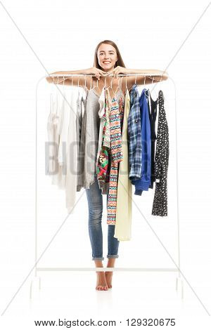 Barefoot smiling brunette tiptoes behind hanger with clothes.Studio shot