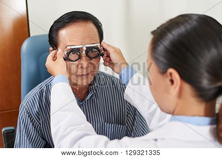 Female ophthalmologist precisely determines diopter for senior man