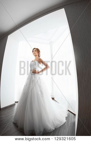 Beautiful young bride in white wedding dress indoors.  Luxuty model standing in full length against big window at home. Girl showing fashion look of wedding dress in bright room. High key, made on fisheye lens photo.