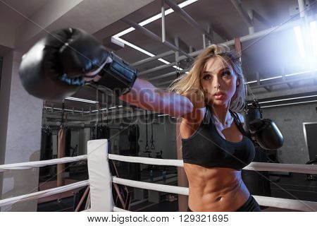 attractive young woman making a punch on the black sandbag in blue glove