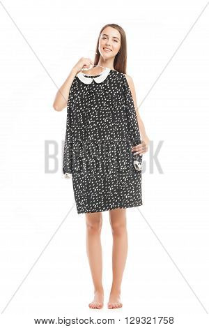 Smiling brunette holding black and white dress on hanger