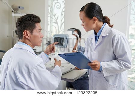 Ophthalmologist giving instructions to nurse when examining patient