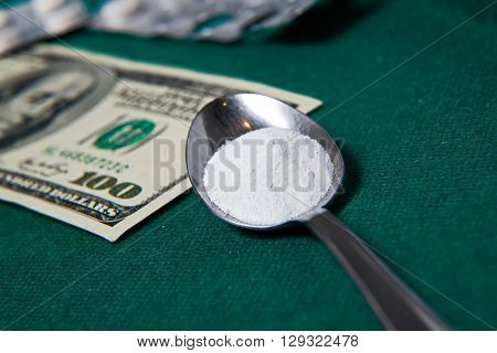 Hard drugs with dollar bills on poker table