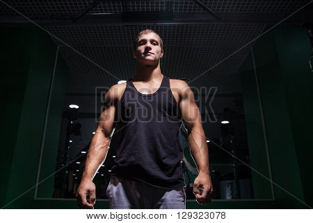 Portrait of young muscular sportsman looking at camera in gym.From below