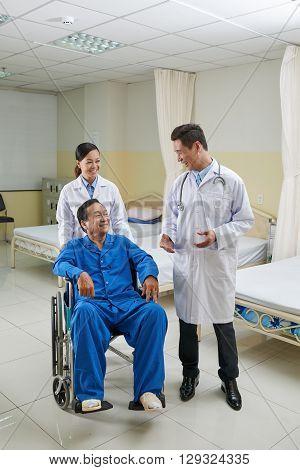 Cheerful Vietnamese doctor talking to disabled senior man