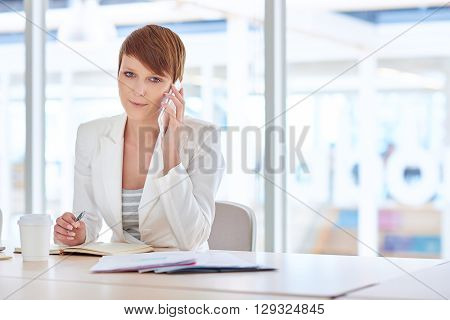 Portrait of a pretty young female business executive looking at the camera with a positive expression, while holding her phone to her ear at her desk