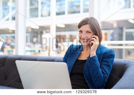 Attractive young businesswoman smiling at the camera, while holding her phone to her ear and sitting on a couch in a modern office space with her laptop computer on her lap