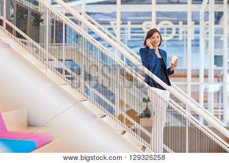 Portrait of a businesswoman standing on a staircase in a bright modern open office holding her phone to her ear and a cup of takeaway coffee, and smiling at the camera