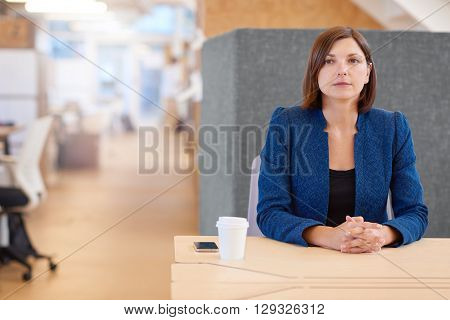 Attractive young businesswoman sitting at her desk in a shared office space, thinking and looking serious yet optimistic