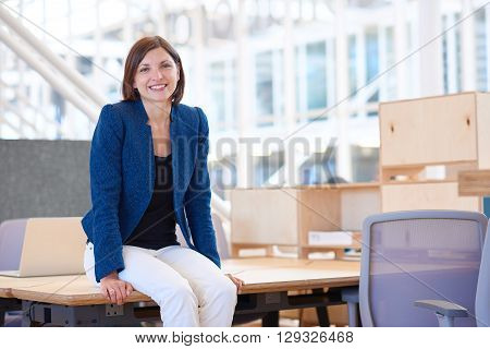Portrait of a relaxed businesswoman in a stylish jacket, smiling warmly at the camera while sitting on the edge of her desk in a bright modern office