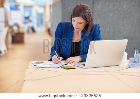 Businesswoman working on paperwork and writing notes at her desk in a shared office space, with her laptop computer open in front of her