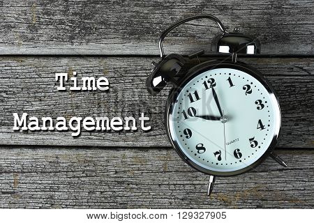 Black alarm clock on the rusty wooden table with word Time Management