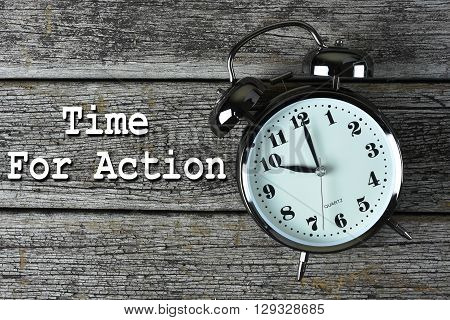 Black alarm clock on the rusty wooden table with time for action