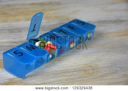 Variety of pills in blue plastic pill organizer box on weathered wood.