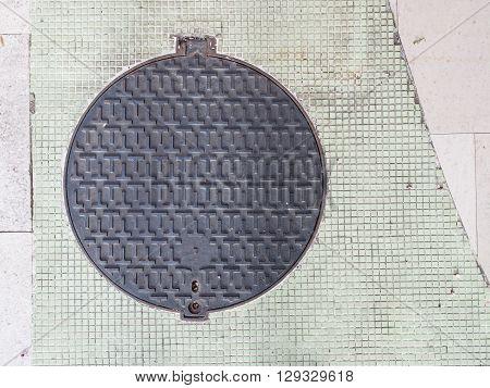 Circle Steel Manhole Cover On Concrete Sidewalk