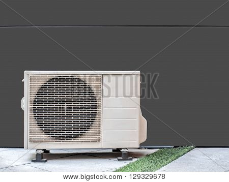 Air conditioning compressor against brown cement wall outside building