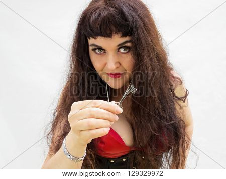 Attractive woman with long hair holding a key. In a red dress with black corset.