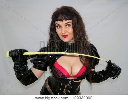 Attractive dominatrix holding a whip in black and red PVC outfit