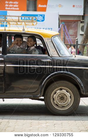 MUMBAI, INDIA - OCTOBER 9, 2015: Unidentified kids in the back seat of the car. Private vehicles account for 30% of the total transport demand in urban areas of India.