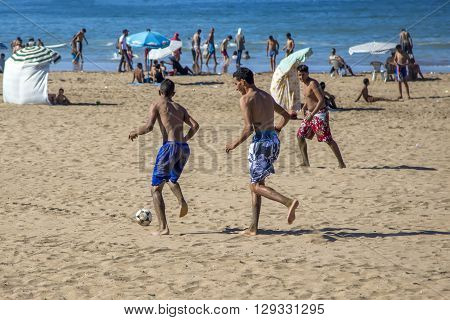 RABAT, MOROCCO - SEPTEMBER 10, 2014: Unidentified people playing soccer at the beach. Soccer is a very popular sport in Morocco.