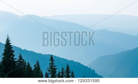 Abstract mountain background - concept of tourism and mountaineering. Layers of ridges in Carpathians Mountains Ukraine at sanrise sky