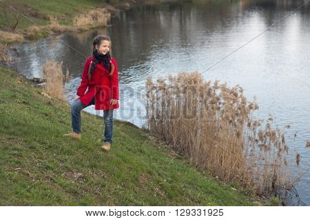 girl in red raincoat and jeans on the to the river