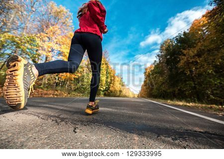 Lady in sportswear running along the road in the autumn forest
