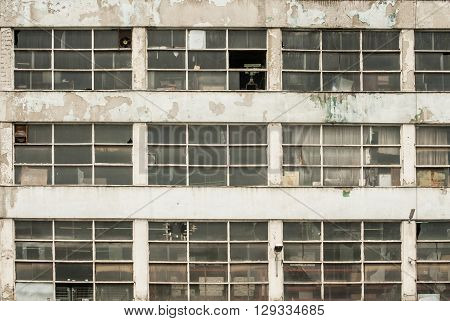 Facade of obsolete weathered grunge industrial building as background