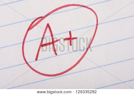 A plus (A+) grade written in red pen on notebook paper.