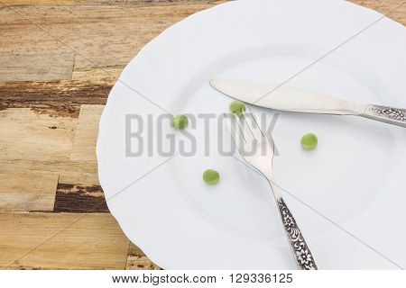 Fresh Green Peas On Plate With Fork And Knife Closeup, On Wooden Surface