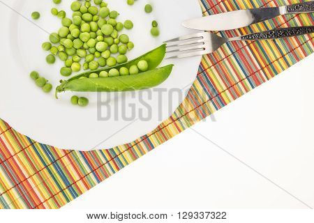 Fresh Green Peas On Plate With Fork And Knife Closeup, On Colorful Bamboo Placemat With Copy-space