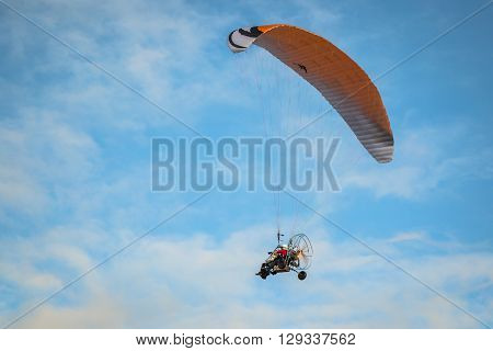 The motorized hang glider in the blue sky