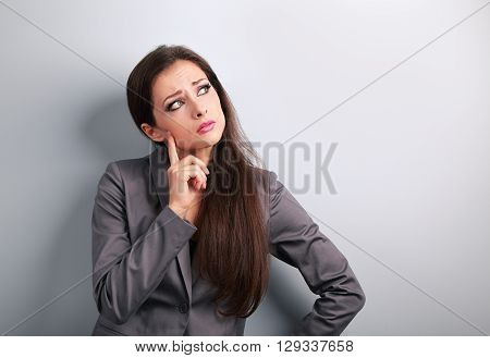 Thinking Unhappy Business Woman In Suit Looking On Blue Empty Copy Space Background