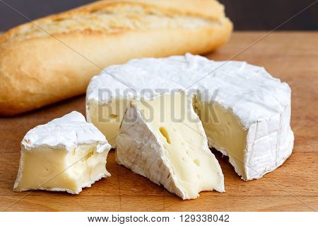 White Mould Cheese With Cut Slices Half Eaten, And Baguette, Isolated On Wood Board.