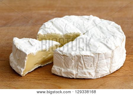 White Mould Cheese With Cut Slice Isolated On Wood Board.