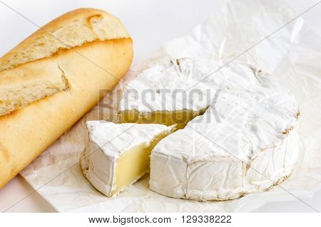 Detail Of White Mould Cheese In Wrapping With Baguette On White.