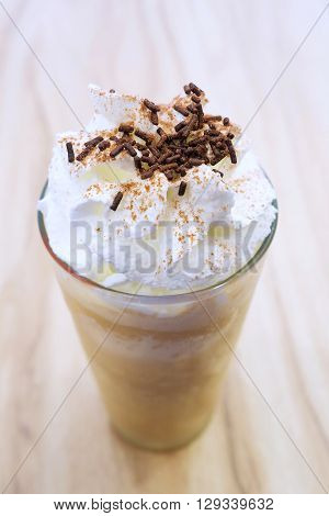 Coffee cappuccino frappe on the table topping whip cream and chocolate.