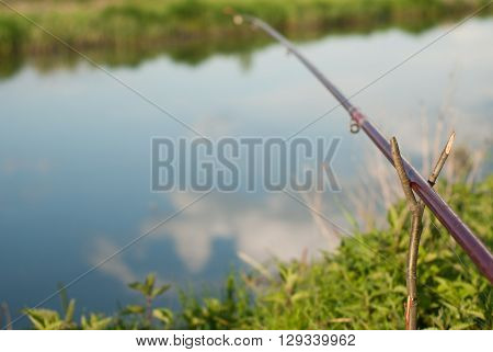 Fishing: fishing rod on the Bank of the river the sky reflected in the water of the river