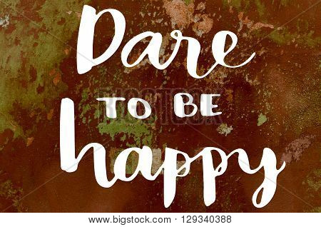 Dare to be happy hand lettering on old painted wall