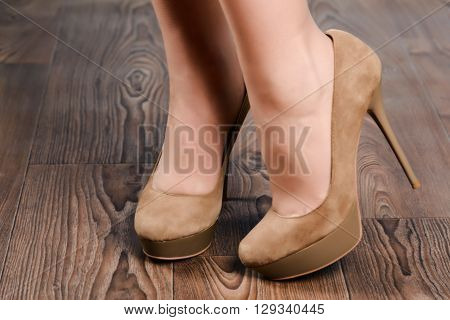 Girl in beige suede high-heeled shoes on the wooden floor