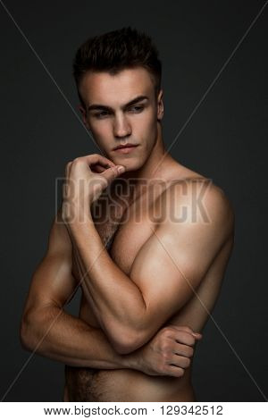 Portrait of a young fashion topless man isolated on dark background