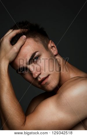 Fashion man portrait with his hand in his hair on dark background