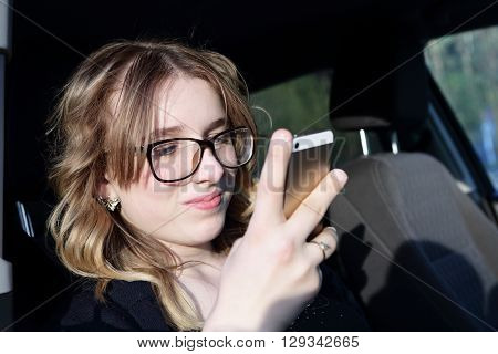 Smiling teen with smartphone in the car
