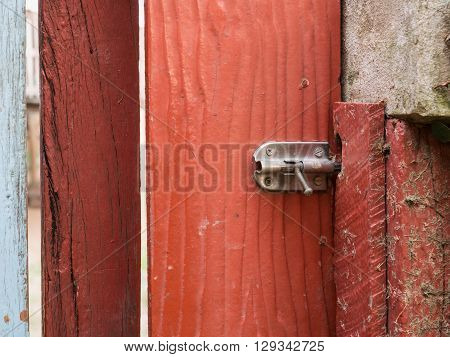 Stainless steel bolt on the red wooden door selective focus on bolt