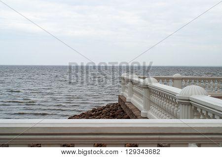 Sea horizon view with white balustrade on the shore