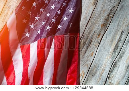 American flag in the sunlight. Flag on white wooden background. Banner of great country. Freedom and equality.