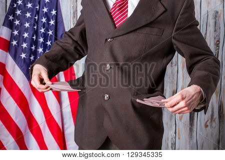 Businessman shows empty pockets. US flag behind man's back. Crisis came suddenly. Governor has too many debts.