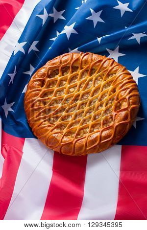 US flag and a pie. Baked product laying on flag. Value the traditions. Feel yourself at home.