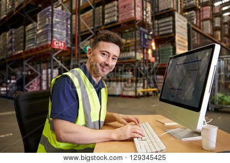 Man at computer in on-site warehouse office looks to camera