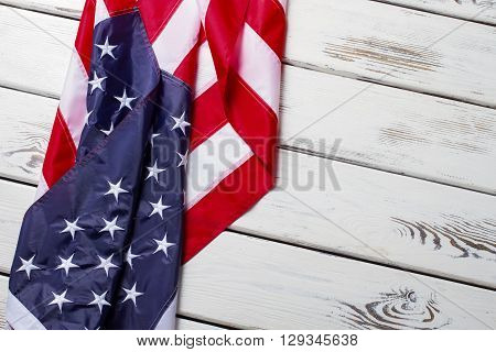 Crumpled USA flag. USA flag on wooden background. Banner laying on white shelf. Greetings from land of opportunity.